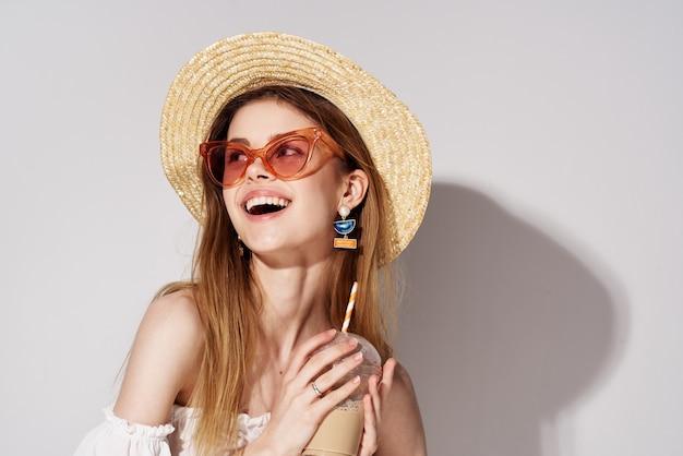 ファッショナブルなメガネと帽子の装飾チャームドリンクモデルの美しい女性。