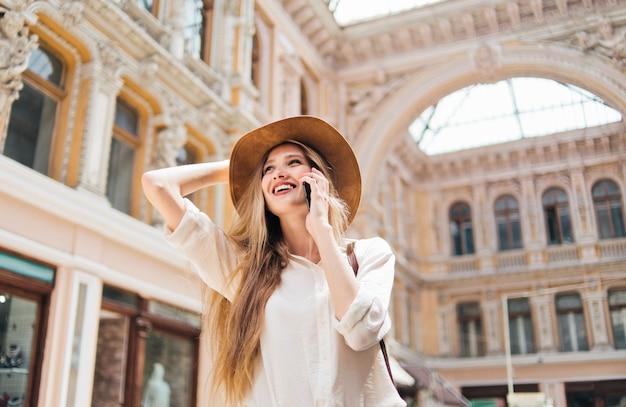 電話で話しているフェルト帽子で美しい女性