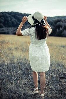 麦わら帽子のフィールドで美しい女性夏のフィールドで幸せな女性若い女の子は屋外でリラックス