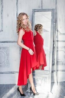 Красивая женщина перед зеркалом в роскошном интерьере в красном платье