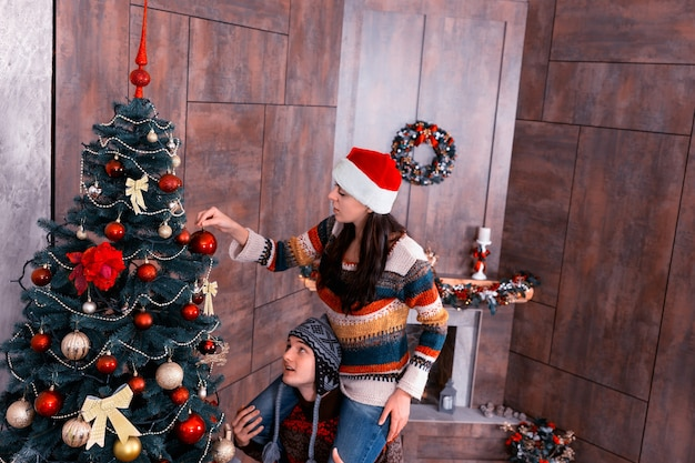 彼女のボーイフレンドの首に座って、装飾された暖炉のあるリビングルームの大きなクリスマスツリーに装飾を掛ける面白い帽子の美しい女性
