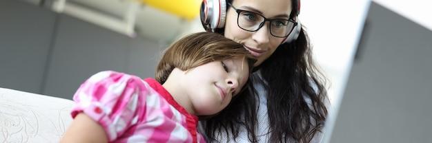 안경 및 헤드폰에서 아름 다운 여자는 노트북을 위해 작동합니다.