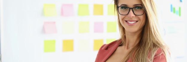 안경 및 긴 머리를 가진 아름 다운 여자 접힌 손으로 서. 배경에는 다채로운 스티커가 붙은 화이트 보드가 있습니다.