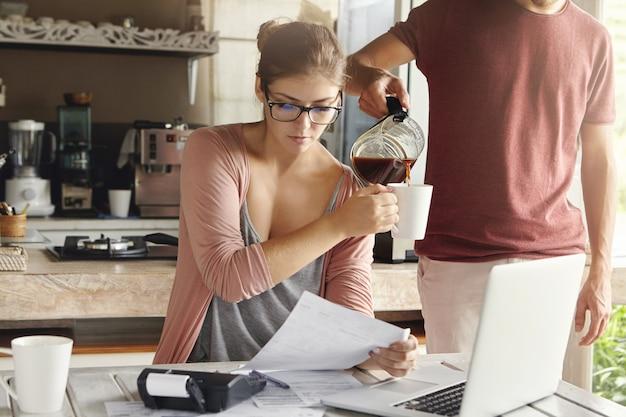 Красивая женщина в очках, держа лист бумаги, делая документы и платя налоги за кухонным столом с портативным компьютером и калькулятором на нем. ее муж стоит рядом и наливает кофе ей в кружку