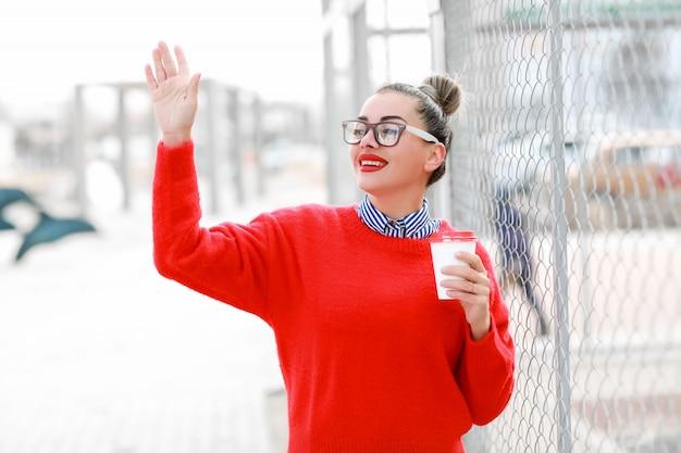 メガネ、赤いセーター、コーヒーのグラスが付いている通りを歩いて赤い口紅で美しい女性