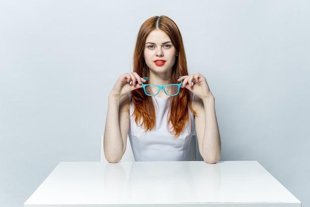 メガネで美しい女性がテーブルの明るい背景に座っています。