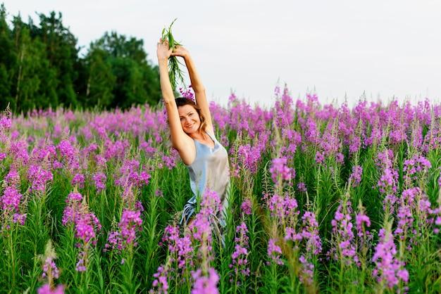 Красивая женщина в сером платье радуется с поднятыми руками и букетом цветов на лугу кипрея