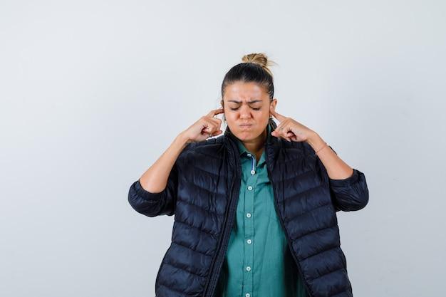 緑のシャツを着た美しい女性、人差し指で耳を塞いでいる黒いジャケット、目を閉じて怒っているように見える、正面図。