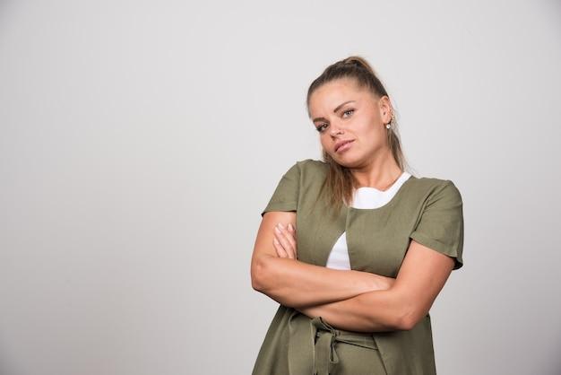 Красивая женщина в зеленой рубашке позирует на серой стене.