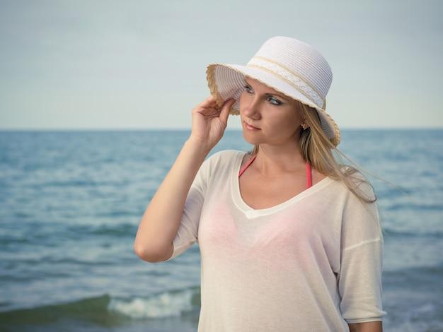 Красивая женщина в шляпе против вечернее море.
