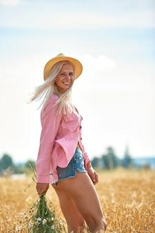 帽子をかぶって、晴れた夏の日にフィールドデイジーのバスケットを持つ美しい女性。