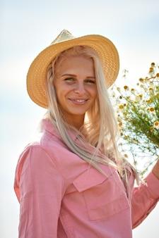 Красивая женщина в шляпе и с корзиной полевых ромашек в солнечный летний день.
