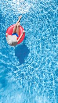 Красивая женщина в шляпе в бассейне с высоты птичьего полета сверху, молодая девушка в бикини расслабляется и плавает на надувном кольцевом пончике и развлекается в воде на семейном отдыхе, тропический курорт