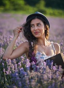 紫色のラベンダー畑に座って本を持っている帽子の美しい女性。