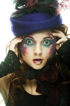 Красивая женщина в шляпе с артистическим макияжем. стиль принцессы.