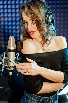 ヘッドフォンで美しい女性。暗いスタジオの背景に女の子。胸に手を組んだ。歌手の肖像画。