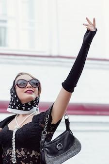 Красивая женщина в платке в стиле ретро на открытом воздухе, глядя вверх, жестикулируя