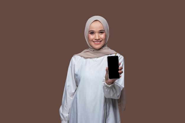 히잡을 쓴 아름다운 여성이 휴대폰을 들고 앞으로 보여주고 있다