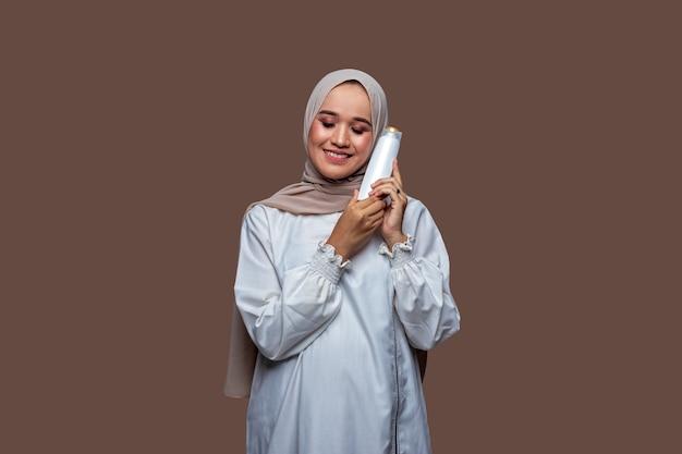 ヒジャーブの美しい女性は、両手でシャンプーボトルを持って、目を閉じて笑顔で左頬に置いています。