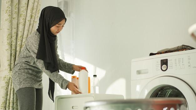 Красивая женщина в хиджабе готовит моющее средство для стирки дома