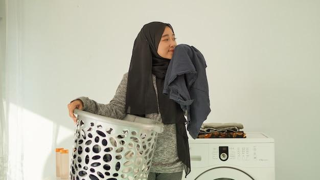 Красивая женщина в хиджабе чувствует запах одежды дома