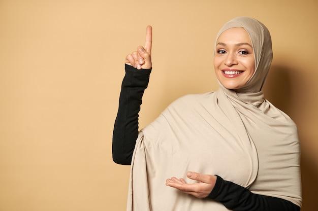 カメラを見て、ベージュの上に指を指して歯を見せる笑顔を笑っているヒジャーブの美しい女性
