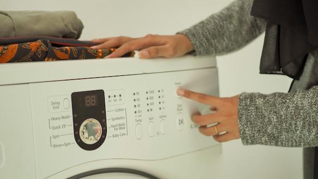 히잡을 쓴 아름다운 여성이 집에서 세탁기를 누르기 시작합니다