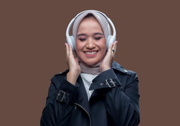 ヒジャーブの美女が目を閉じながら笑顔でワイヤレスヘッドホンを使って音楽を聴いていた