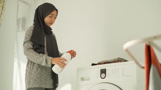 Красивая женщина в хиджабе наливает стиральное средство в свою стирку дома