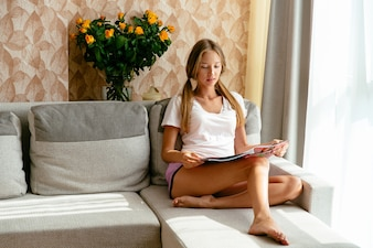 Beautiful Woman in home clothing reading magazine at home on sofa