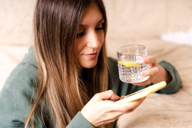 Hoody 문자 메시지와 물 잔을 들고 소파에 앉아 모바일 휴대 전화에서 채팅에서 아름 다운 여자.