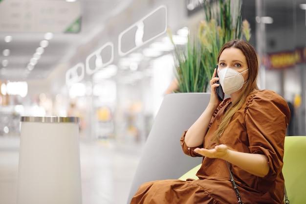 個人保護マスクの美しい女性はショッピングセンターにあり、電話で話しているジェスチャー
