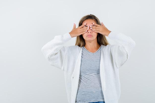 Красивая женщина в куртке, футболке, держа руку над головой и выглядящей усталой, вид спереди.