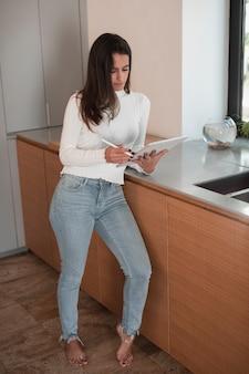 Красивая женщина на кухне, глядя на планшет