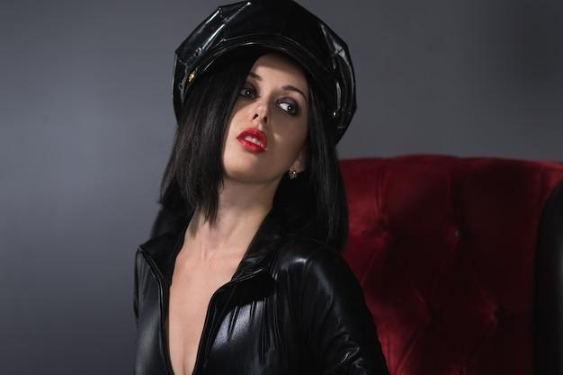 Красивая женщина в латексном костюме в кресле на темном фоне