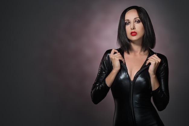 Красивая женщина в латексном костюме на темном фоне