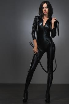 Красивая женщина в латексном костюме с кнутом на темном фоне
