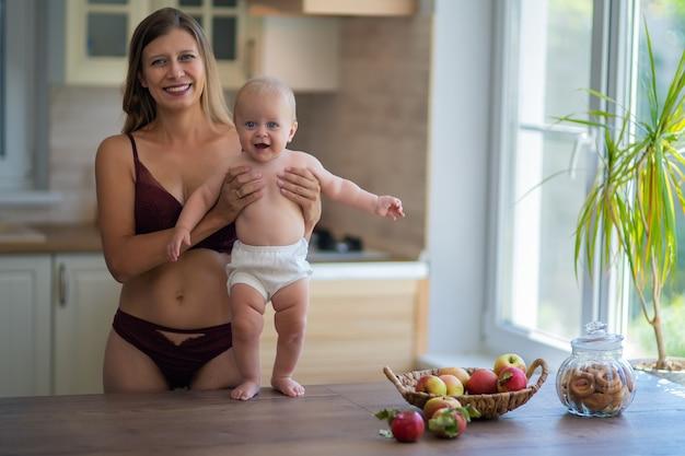 집에서 부엌에서 아기와 함께 란제리를 입은 아름다운 여자