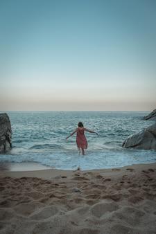 Красивая женщина в длинном оранжевом платье бежит по пляжу на закате