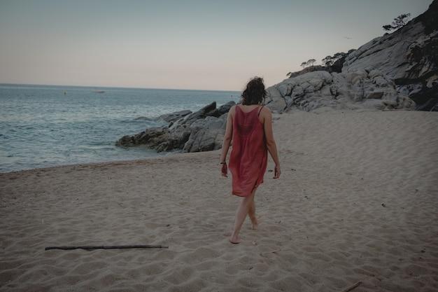 Красивая женщина в длинном оранжевом платье гуляет по пляжу на закате