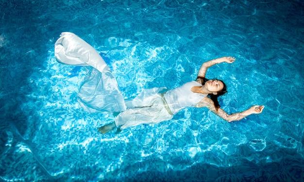 Красивая женщина в длинном белом платье, плавание в бассейне в солнечный день