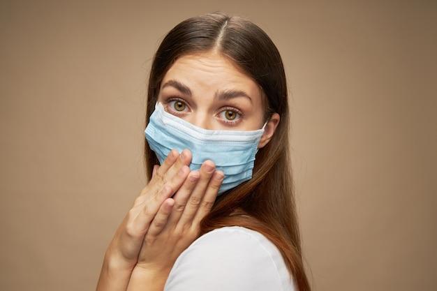 医療マスクで美しい女性は彼女の手とクローズアップの肖像画で顔を覆った