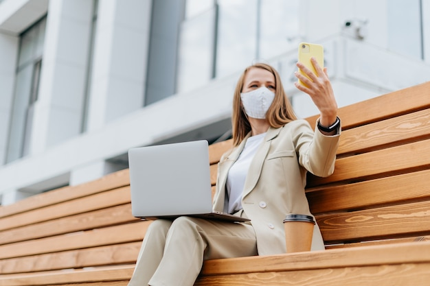 Красивая женщина в медицинской защитной маске, делающей селфи
