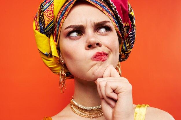 Красивая женщина в разноцветном тюрбане привлекательный вид ювелирных изделий на красном фоне