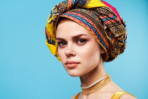 여러 가지 빛깔의 터번을 입은 아름다운 여성이 매력적인 모양의 보석 미소 파란색 배경