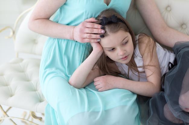 무릎에 딸과 함께 해군 그리스 드레스에서 아름 다운 여자