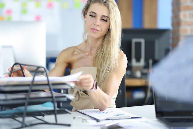 Красивая женщина в офисе берет документ с полки