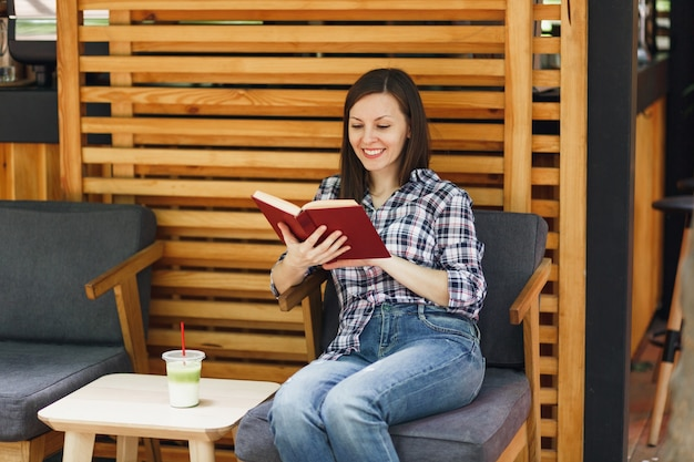 カジュアルな服を着て座って、カクテルのカップで本を読んで、屋外通りの夏のコーヒーショップの木造カフェの美しい女性