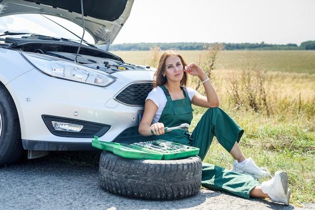 彼女の旅で壊れた車を修理するキーを持つオーバーオールの美しい女性