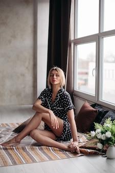 枕とソファに座っているパジャマの美しい女性